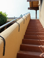 grab railing mounted to the top of a stucco wall